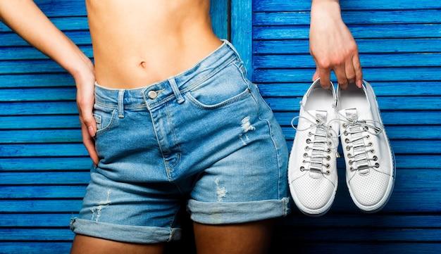 Menina segura um par de sapatos. menina com uma bela cintura em shorts jeans. mulher segurando sapatos em uma parede azul. mulher segurando um par de sapatos brancos.
