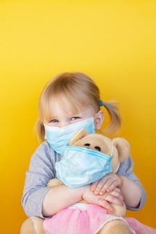 Menina segura um ursinho de pelúcia tanto na máscara médica.