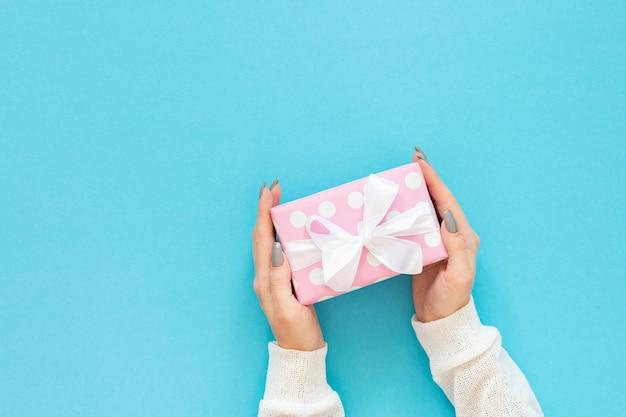 Menina segura uma caixa de presente, caixa de presente rosa em bolinhas com fita branca e arco em um fundo azul, vista plana, vista de cima, aniversário ou dia dos namorados