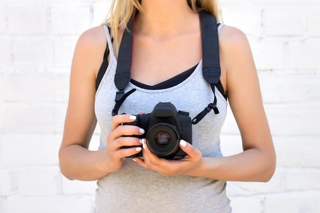 Menina segura uma câmera em um fundo de uma parede de tijolos brancos