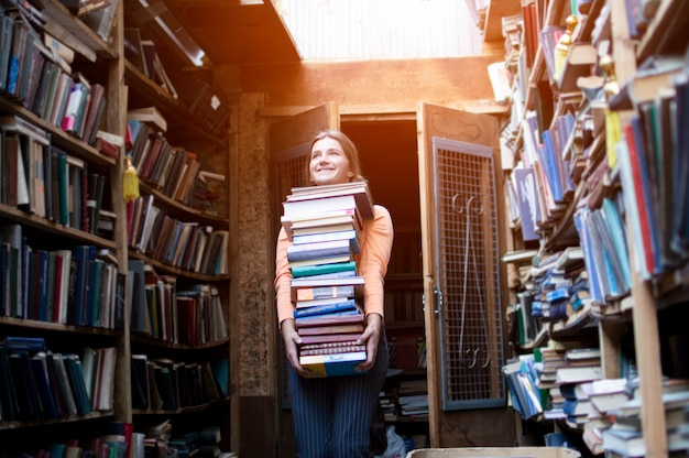 Menina segura uma grande pilha de livros na biblioteca