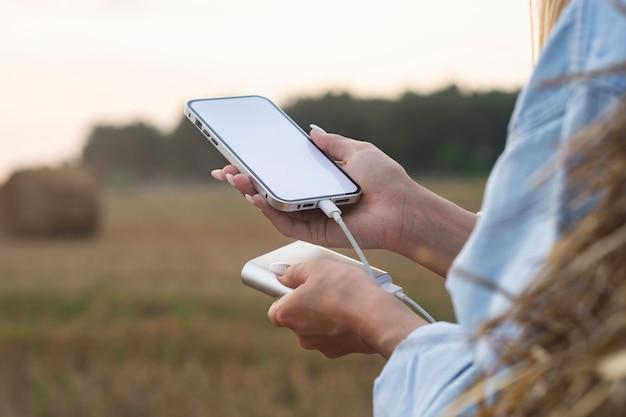 Menina segura uma maquete de um smartphone com uma tela branca nas mãos. power bank carrega o telefone contra o fundo da natureza.