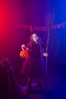 Menina segura vassoura no feriado de halloween, criança, garota, usa fantasia de bruxa fantasia conto de fadas e
