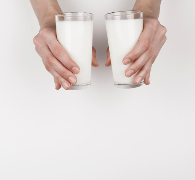 Menina segurando 2 copos de leite