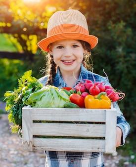 Menina, segurando a caixa de legumes orgânicos frescos