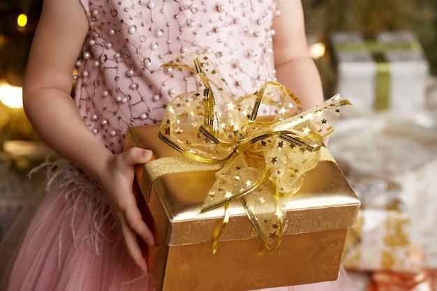 Menina, segurando a caixa de presente dourada
