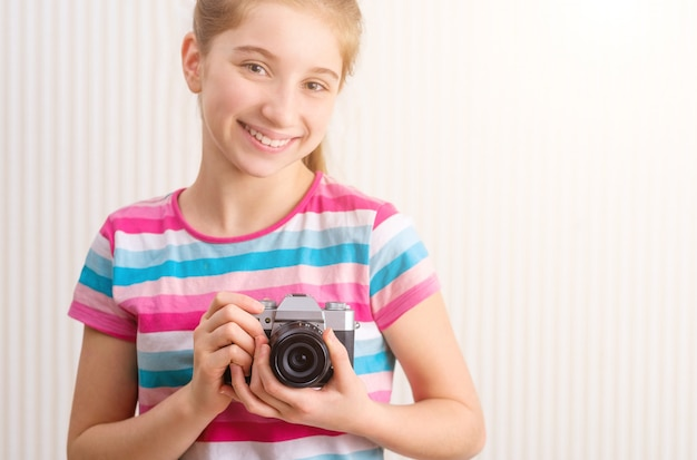 Menina segurando a câmera fotográfica