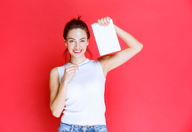 Menina segurando a folha de exame e apontando para ela.