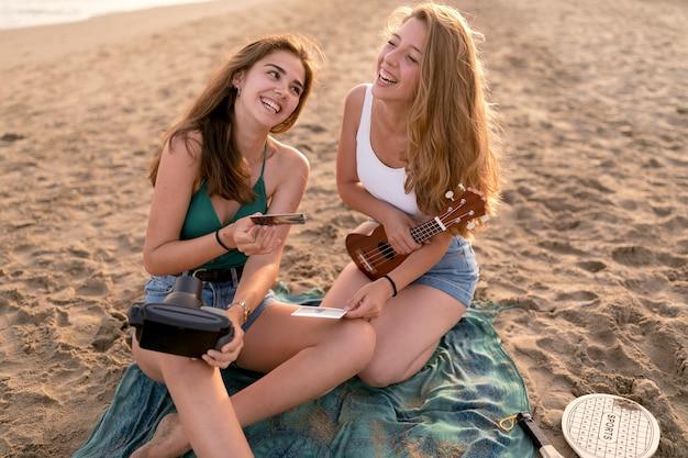 Menina, segurando a imagem instantânea, tirando sarro com a amiga na praia