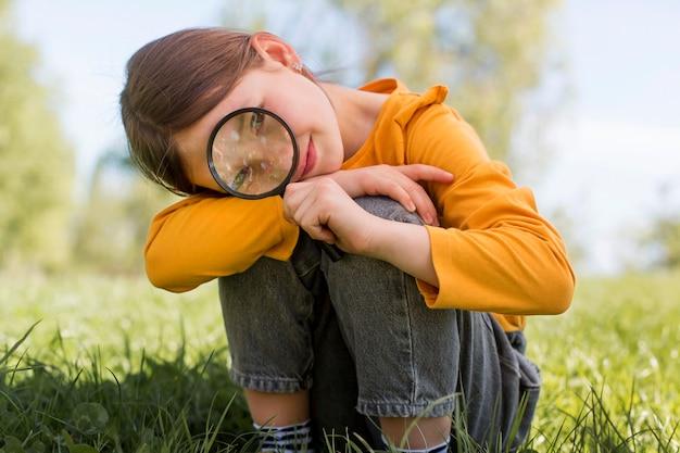 Menina segurando a lente de aumento