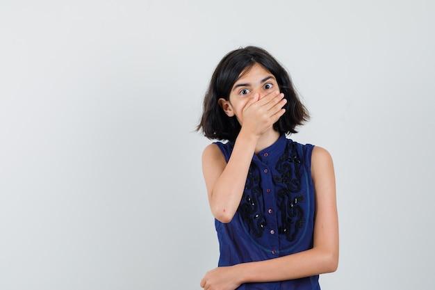 Menina segurando a mão na boca com blusa azul e olhando surpresa, vista frontal.