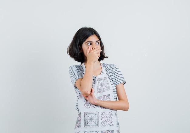 Menina segurando a mão na boca em t-shirt, avental e parecendo surpresa.
