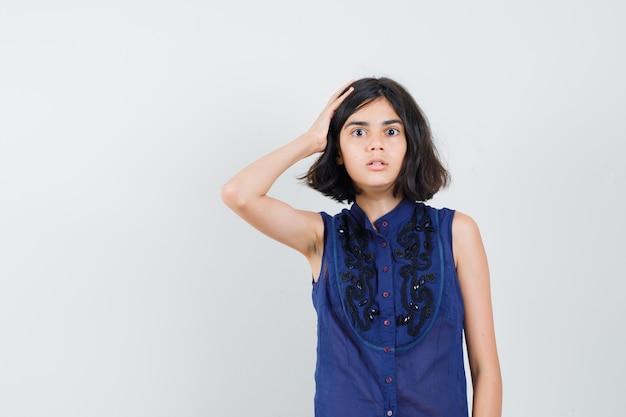 Menina segurando a mão na cabeça com blusa azul e parecendo confusa. vista frontal.
