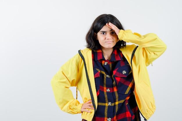 Menina segurando a mão na testa em camisa quadrada, jaqueta e parecendo esquecido. vista frontal.