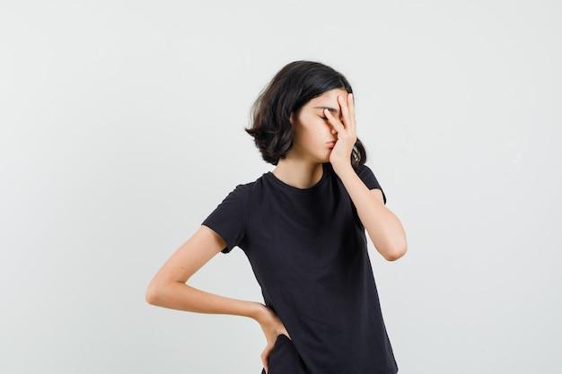 Menina segurando a mão no rosto em t-shirt preta e olhando com sono, vista frontal.