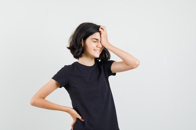 Menina segurando a mão no rosto em t-shirt preta e parecendo envergonhada, vista frontal.