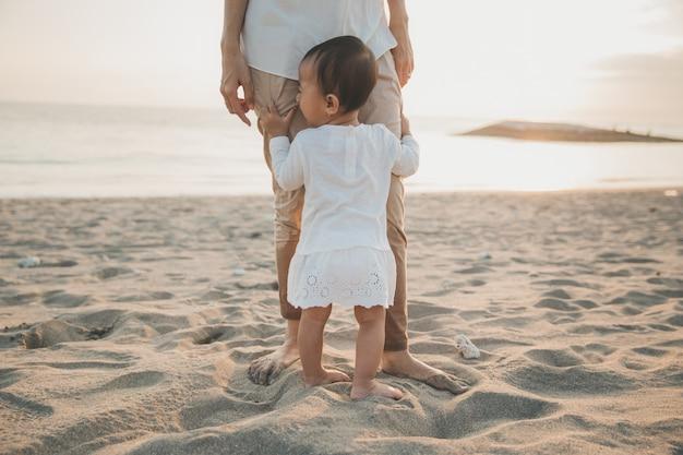 Menina, segurando a perna da mãe em pé na praia