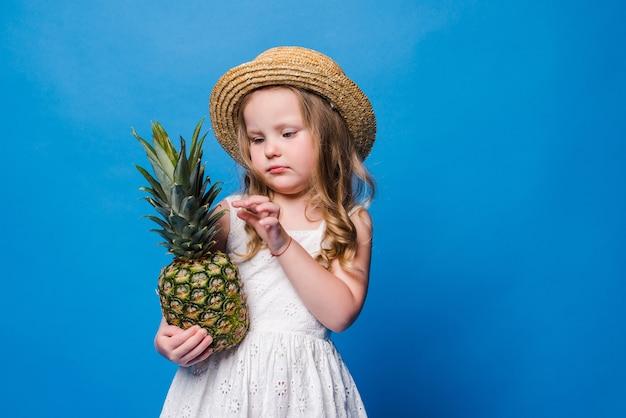 Menina segurando abacaxi inteiro na parede azul com espaço de cópia