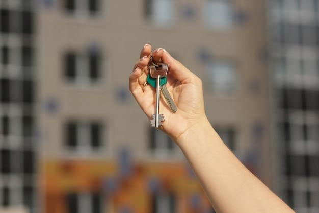 Menina segurando as chaves do novo apartamento close-up, fundo desfocado