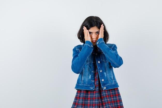 Menina segurando as mãos na cabeça na camisa, jaqueta e parecendo impotente, vista frontal.