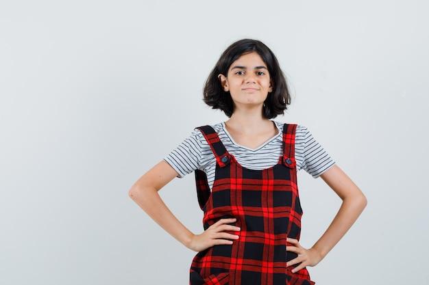 Menina segurando as mãos na cintura com um vestido avental e parecendo confiante,