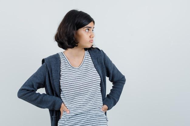 Menina segurando as mãos na cintura em uma camiseta, jaqueta e parecendo confusa.