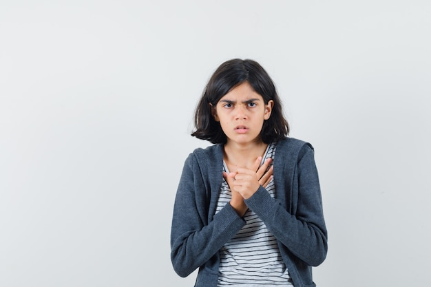 Menina segurando as mãos no peito em camiseta, jaqueta e parecendo perplexa.