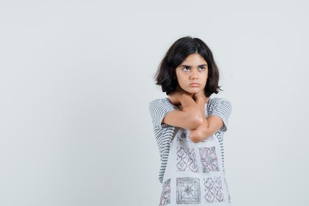 Menina segurando as mãos no pescoço em uma camiseta, avental e parecendo chateada,