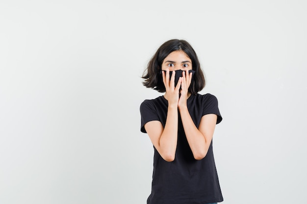 Menina segurando as mãos no rosto em camiseta preta, máscara e olhando espantado, vista frontal.