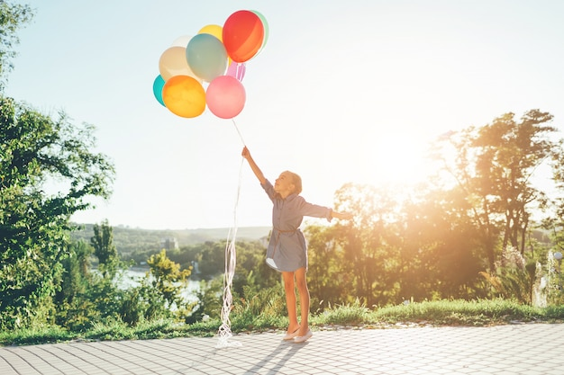 Menina segurando balões coloridos, estendendo-se para o céu