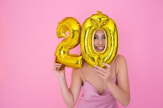 Menina segurando balões de papel alumínio na forma de números, vendas com desconto de vinte por cento e reembolso