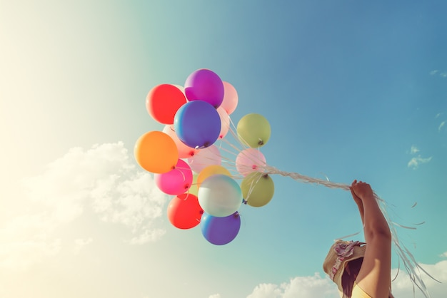 Menina segurando balões multicoloridos