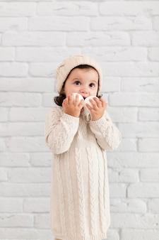 Menina segurando bolas de neve perto do rosto