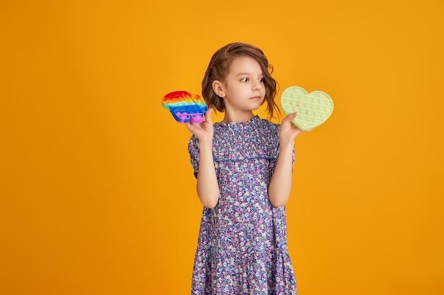 Menina segurando brinquedo anti-stress em amarelo