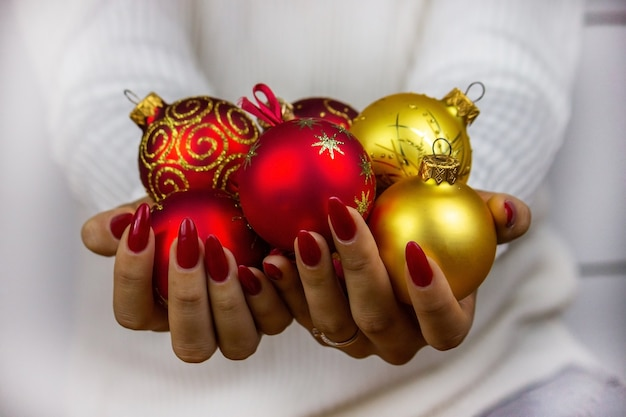 Menina segurando brinquedos, presentes e relógios de ano novo nas mãos dela. conceito de natal.