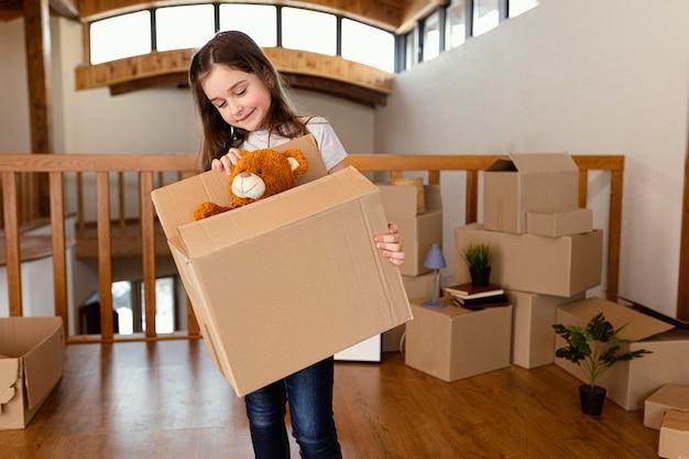 Menina segurando caixa com brinquedo tiro médio