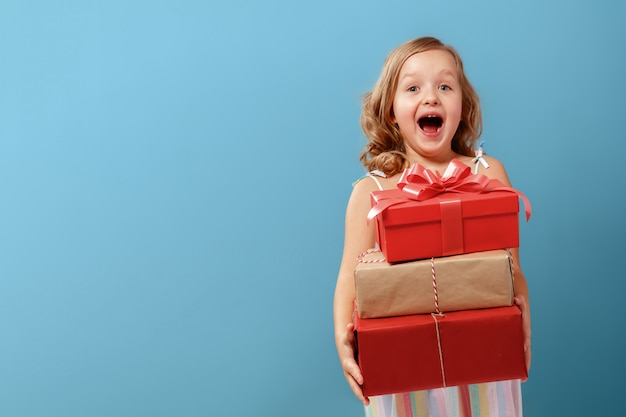 Menina segurando caixas com presentes.