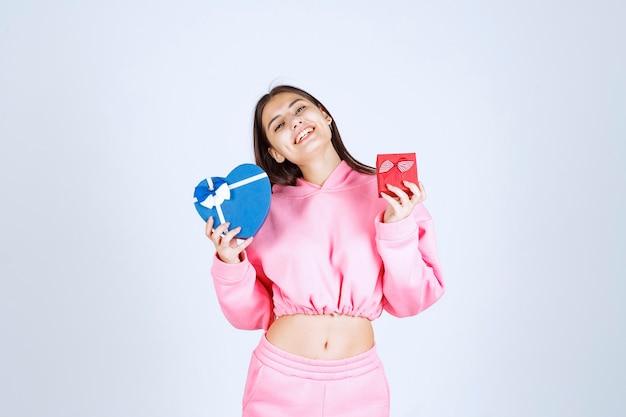 Menina segurando caixas de presente azuis e vermelhas com as duas mãos.