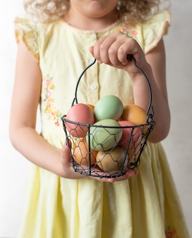 Menina segurando cesta com ovos de páscoa pastel. conceito de feliz páscoa