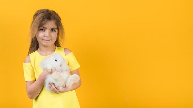 Menina segurando coelho branco