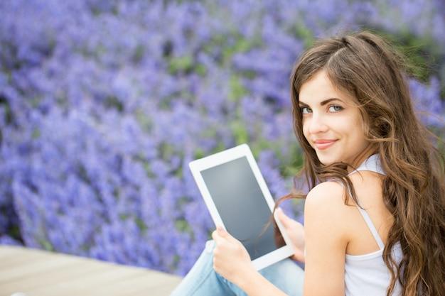 Menina segurando computador tablet e sorrindo