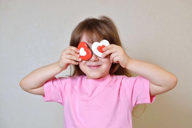 Menina segurando corações em vez de olhos. conceito de feliz dia dos namorados.