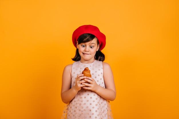 Menina segurando croissant. criança morena com boina francesa expressando espanto na parede amarela.
