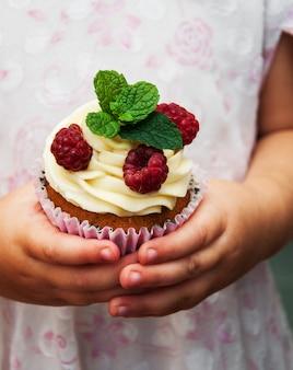 Menina segurando cupcake