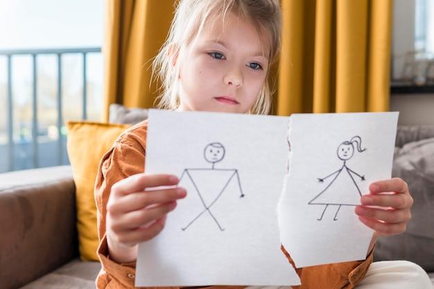 Menina segurando desenho quebrado