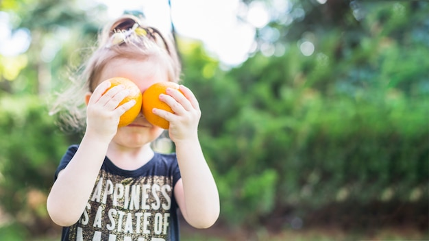 Menina, segurando, dois, laranjas, sobre, dela, olhos