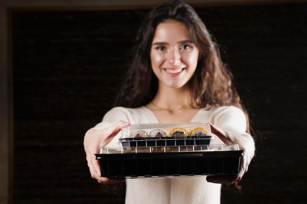 Menina segurando duas caixas de sushi em fundo preto