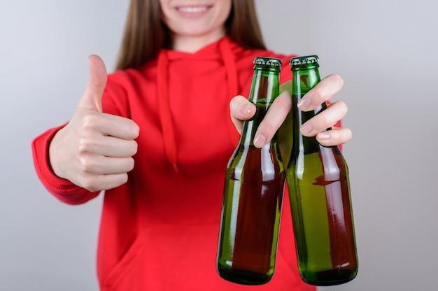 Menina segurando duas garrafas de cerveja com o polegar para cima