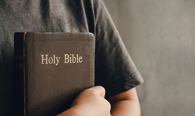 Menina segurando e abraçando uma bíblia ao amanhecer unindo as mãos em oração bíblica no culto de conceitos cristãos e espaço de cópia de religião