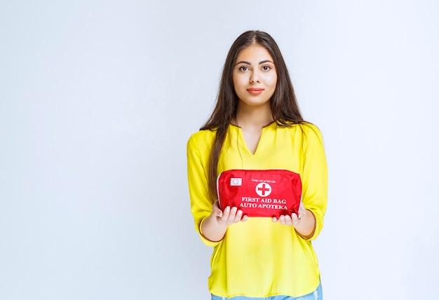 Menina segurando e promovendo um kit de primeiros socorros vermelho.